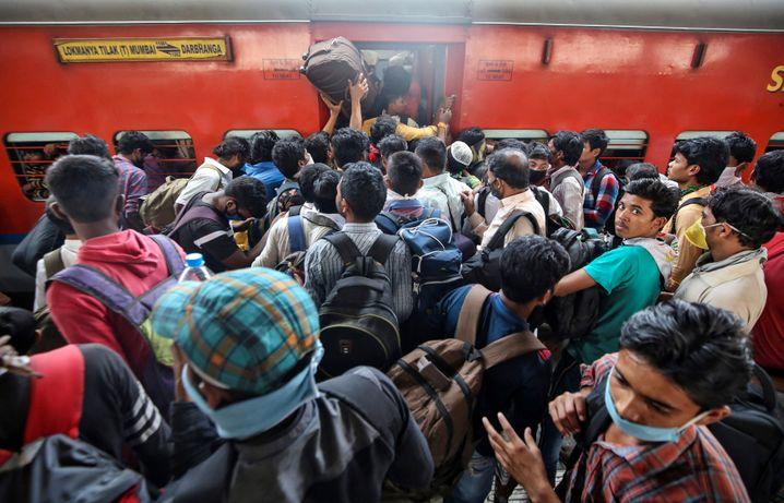 Nichts geht mehr: Dutzende Wanderarbeiter versuchen, sich in einen der letzten Züge zu quetschen