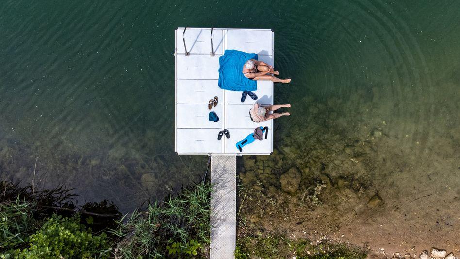 Zwei Frauen sitzen auf einem Steg am Lieblsee in Bayern