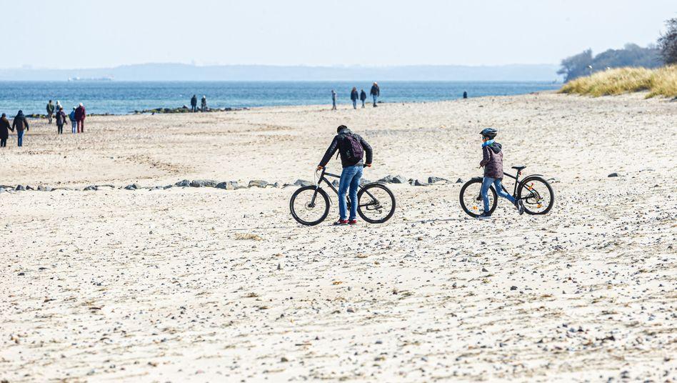 Spaziergänger und Radfahrer am Ostseestrand von Niendorf