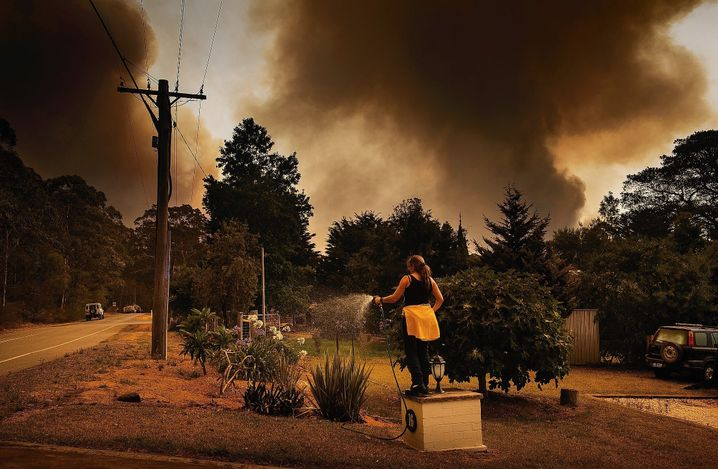 """A homeowner in the Australian town of Tomerong attempting to protect her house from fire. """"They will probably not stop until there is enough rain."""""""