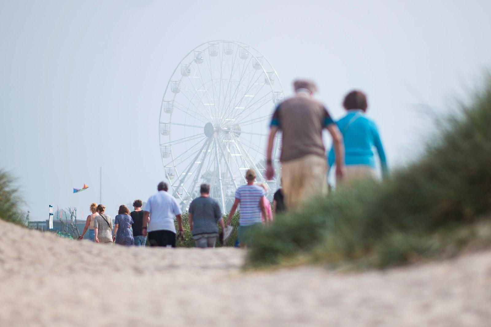 Urlaub in Deutschland Touristen verlassen im Urlaubsort Schillig den Strand und gehen Richtung Promenade, wo ein Riesenr