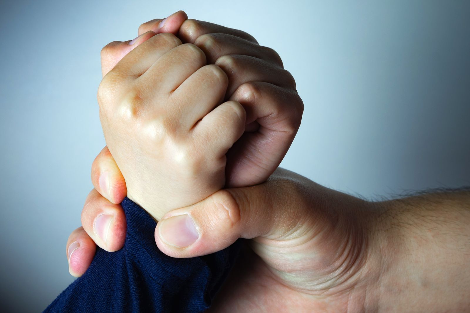 Father roughly holds the hands of his son. Child abuse, domestic violence.