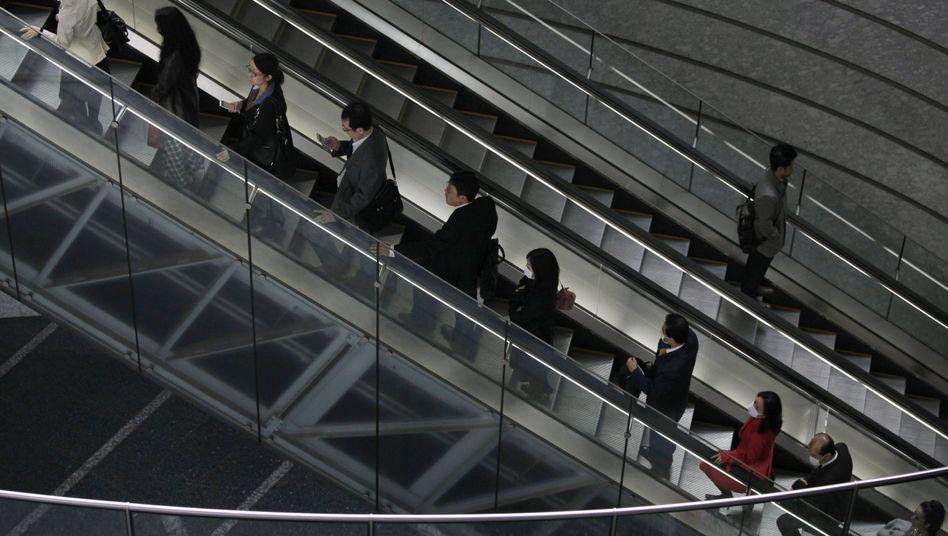 Japanische Pendler auf einer Rolltreppe: Die Notenbank will die Inflation treiben