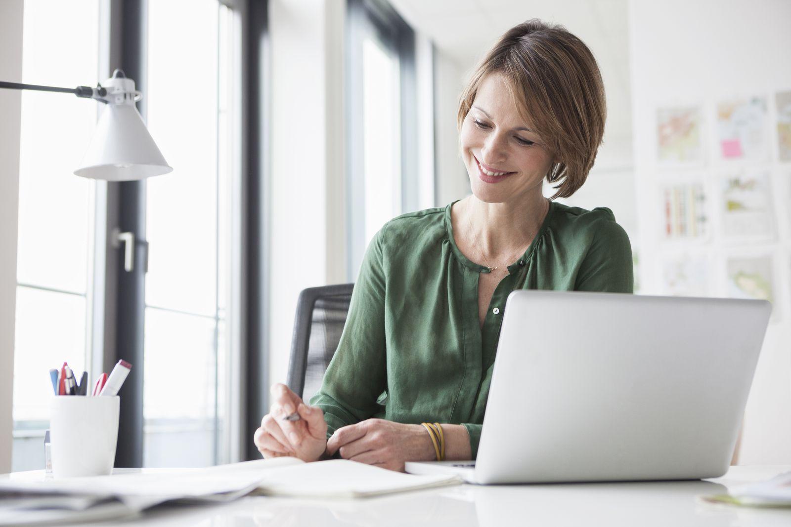 EINMALIGE VERWENDUNG Frau arbeitet am Schreibtisch