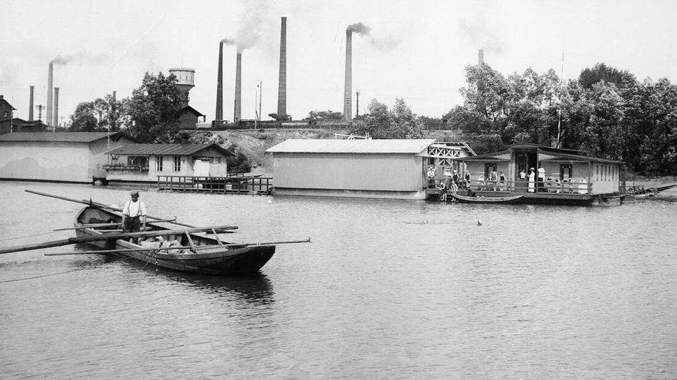 Das Bootshaus des firmeneigenen Ruderklubs:Neben der Rheinbadeanstalt vor rauchenden Bayer-Schloten (um 1910)