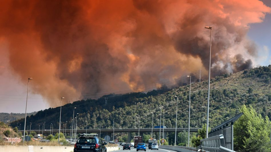 A cloud of smokes rises from a brush fire in Catalonia.