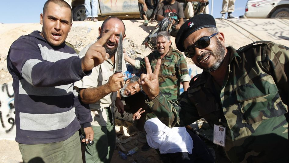 Revolutionary fighters celebrate at the drain where Gadhafi was found on Oct. 20.