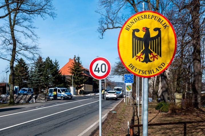 Deutsche Polizeibeamte kontrollieren ein Fahrzeug am tschechisch-deutschen Grenzübergang Petrovice/Bahratal (Februar 2021)