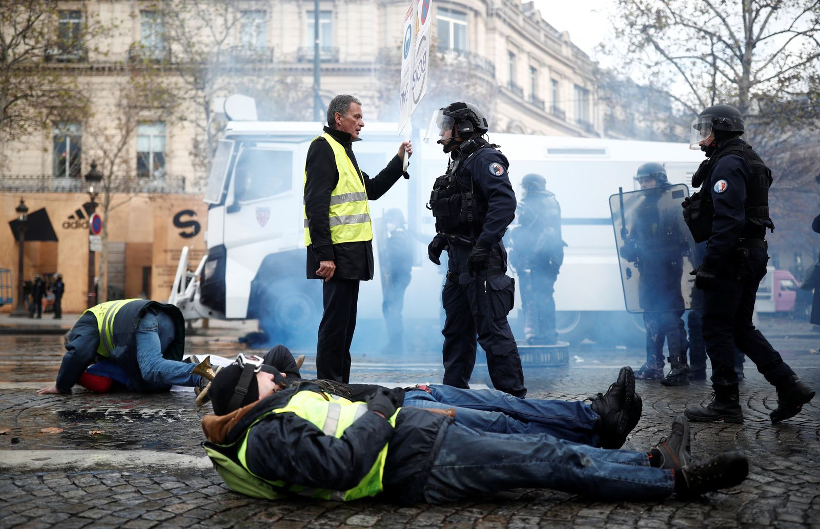 A protester wearing yellow vest, a symbol of a French drivers' protest against higher fuel prices, talks to the police officer during clashes on the Champs-Elysees in Paris