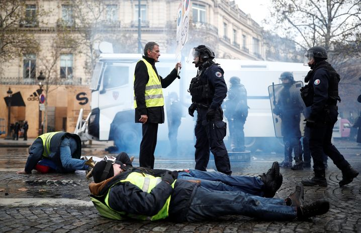 A protester wearing yellow vest, a symbol of a French drivers' protest against higher fuel prices, talks to the police officer during clashes on the Champs-Elysees in Paris, France, November 24, 2018. REUTERS/Benoit Tessier - RC132A15AFD0