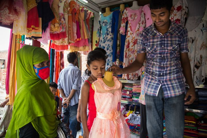 Tasnia Begum's daughter, Mim, chooses a dress for herself for the Eid holiday at a market.