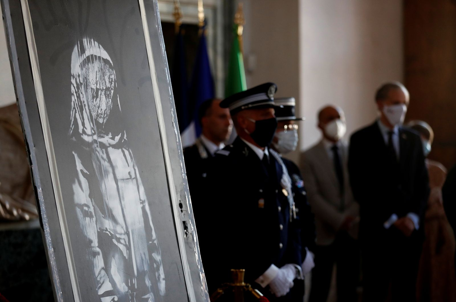 A mural by anonymous British street artist Banksy is seen during the ceremony to return to France at the French embassy in Rome