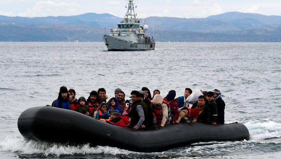 Migranten auf einem Schlauchboot in der Ägäis, im Hintergrund ein Frontex-Schiff (Symbolbild)
