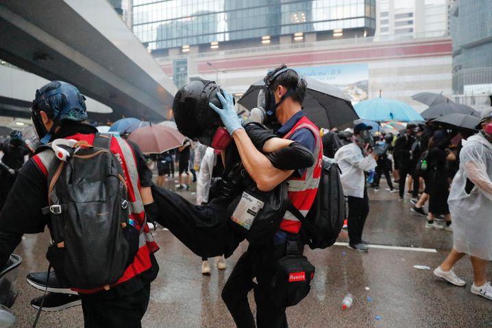 Zwei Demonstranten tragen einen Verletzten