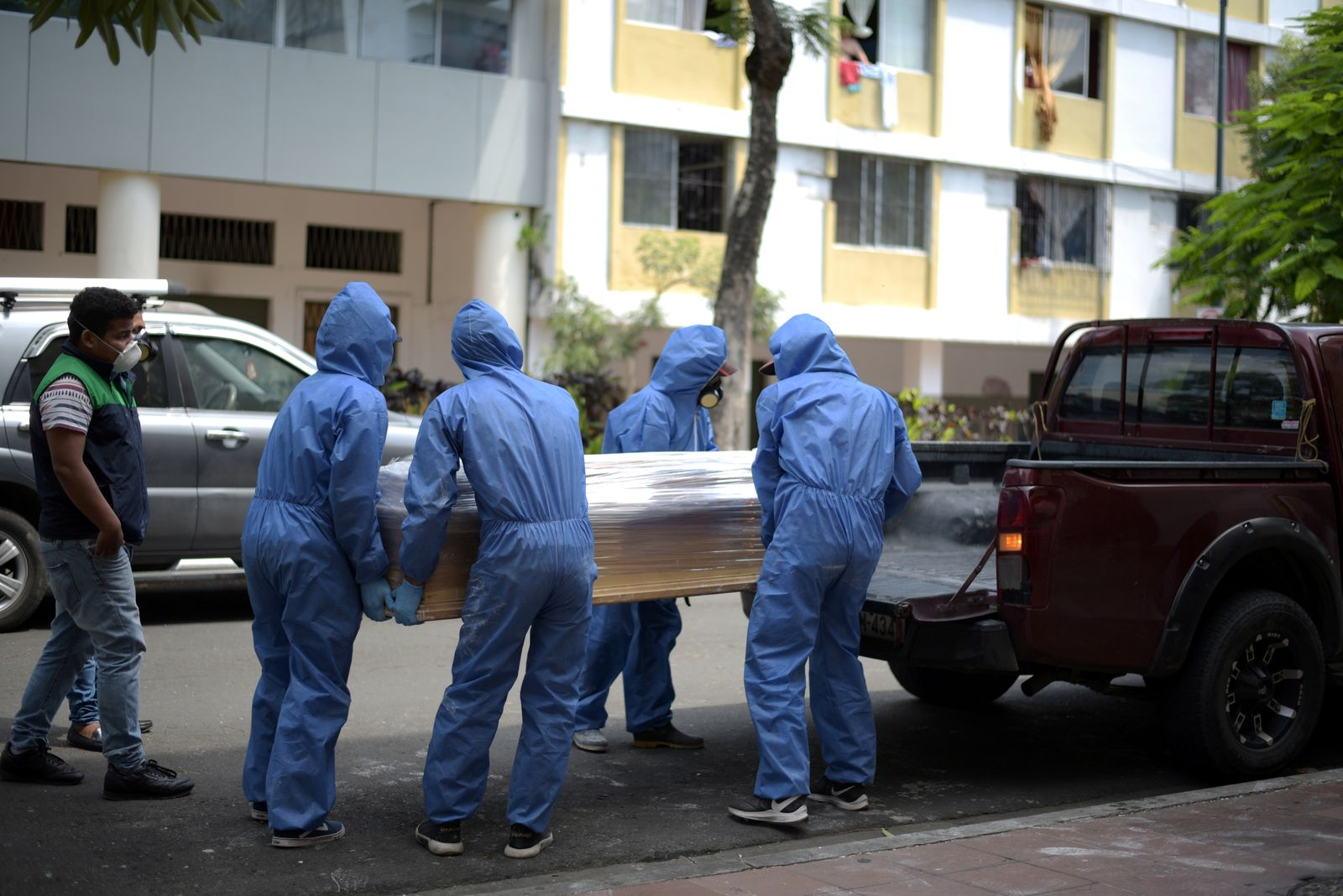 Funeral home workers in protective gear load a coffin containing the body of a man as the coronavirus disease (COVID-19) overwhelms sanitary authorities, in Guayaquil