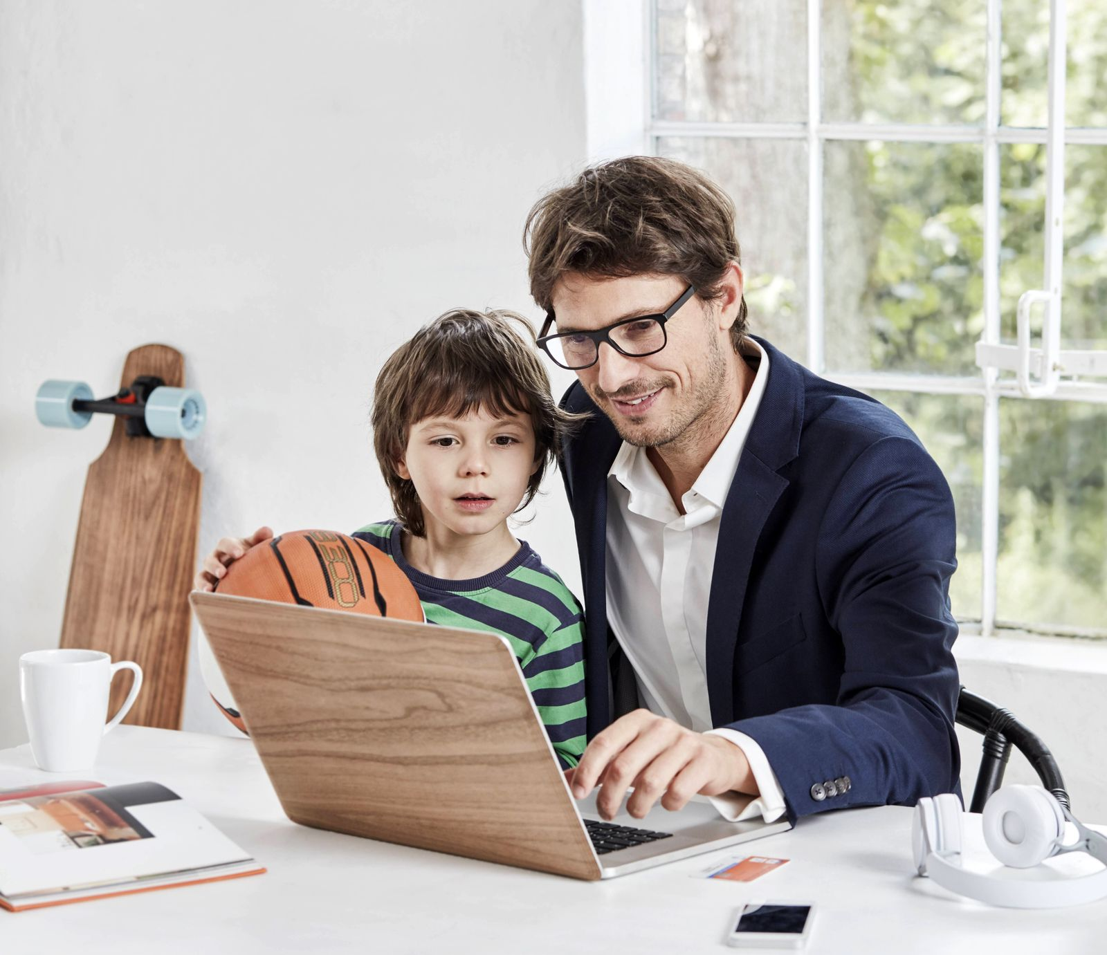 Businessman and son using laptop at desk model released Symbolfoto property released PUBLICATIONxINx