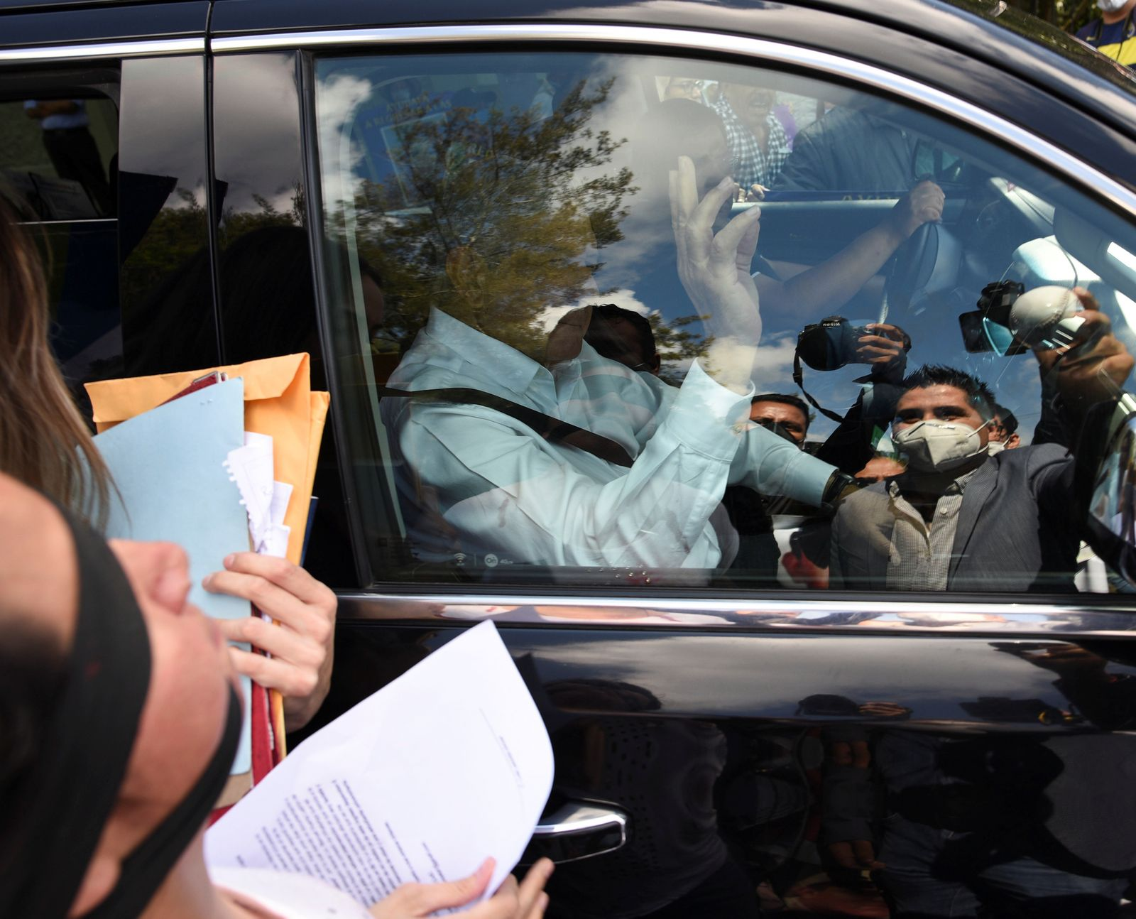 Mexico's President Andres Manuel Lopez Obrador waves from inside a vehicle as relatives of missing people surround to ask him to stop and step down to talk to them, outside the 26-A Military Camp in El Lencero