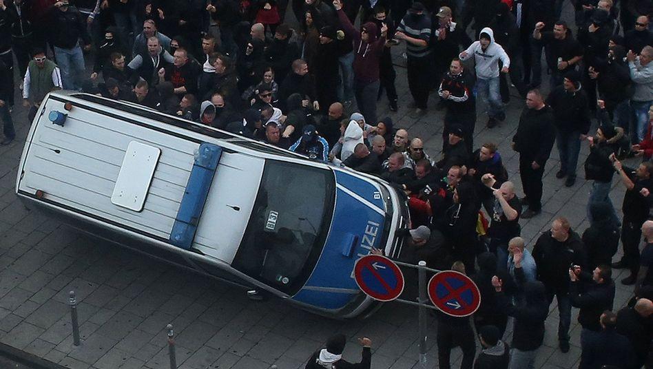 Hogesa-Teilnehmer werfen am 26. Oktober 2014 in Köln ein Polizeiauto um: Drei Jahre Haft für Beteiligten