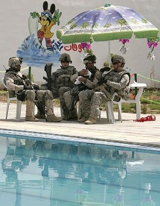 "US and Iraqi soldiers sit together as they guard the newly opened Mithaq swimming pool in Baghdad's Sadr City: ""The level of violence is considerably down."""