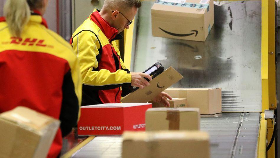 DHL-Mitarbeiter sortieren Pakete (Archivbild)