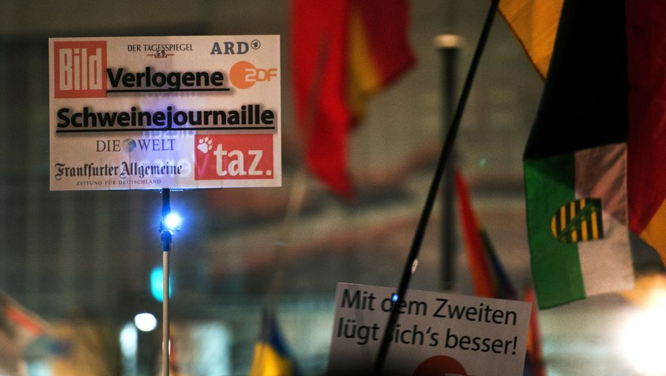 """""""Mendacious swine journals"""" reads this sign held by a German protester at a recent PEGIDA demonstration in Dresden, listing various German media outlets."""
