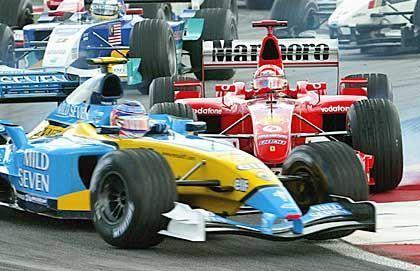 Asphaltrempelei: Michael Schumacher drängt den den vor ihm liegenden Jarno Trulli auf die Wiese