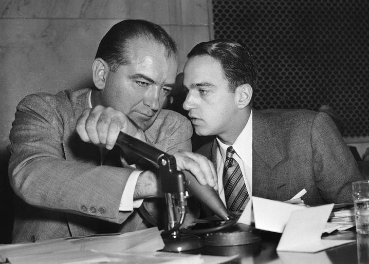 Die rechte Hand des Kommunisten-Jägers: Joseph McCarthy (l.), Rechtsaußen-Senator aus Wisconsin, bespricht sich 1954 mit seinem Chefjuristen, dem damals noch jungen Roy Cohn (r.). McCarthy hatte es sich zur Aufgabe gemacht, Kommunisten in den USA aufzuspüren - und gnadenlos zu bekämpfen. Cohn half ihm dabei.