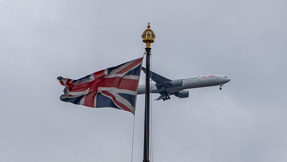 Ein Flugzeug fliegt an einer gehissten Fahne Großbritanniens vorbei (Archivfoto)