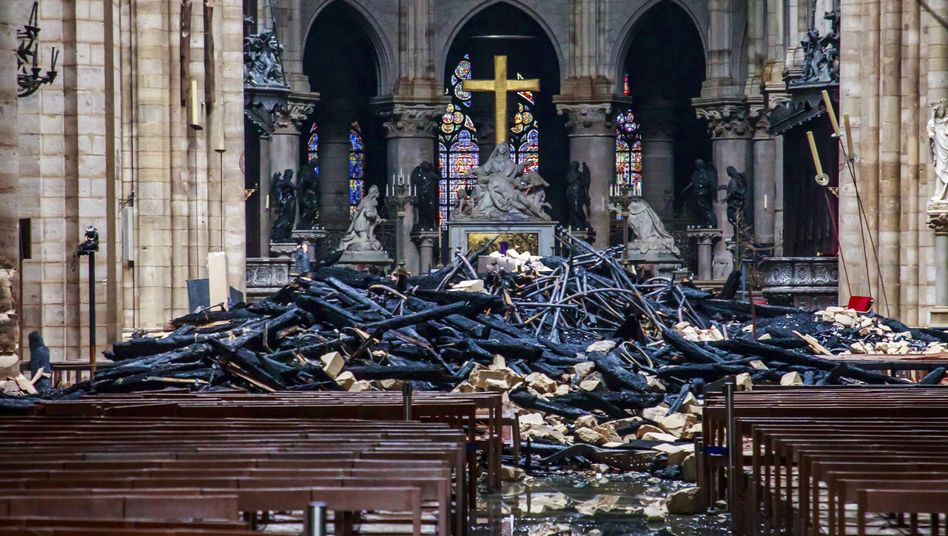 Trümmerteile und verkohlte Holzbalken im Inneren der Kathedrale Notre-Dame
