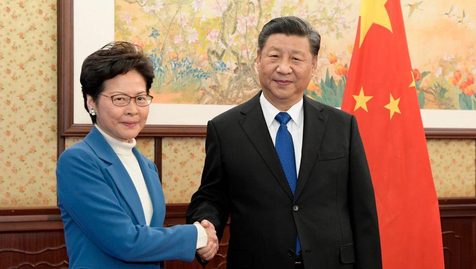 """Hongkongs Regierungschefin Carrie Lam und Chinas Präsident Xi Jinping im Dezember 2019: In der Stellungnahme der chinesischen Botschaft wurde die Verschiebung der Wahl in Hongkong um ein Jahr wegen der Corona-Pandemie als """"vernünftig"""" verteidigt"""