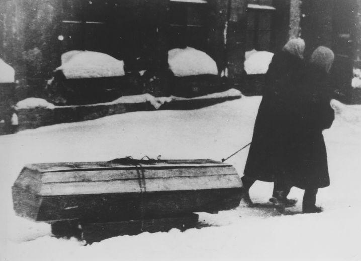 Allgegenwärtiger Tod: Zwei alte Frauen ziehen einen Sarg durch das verschneite Leningrad (1941).
