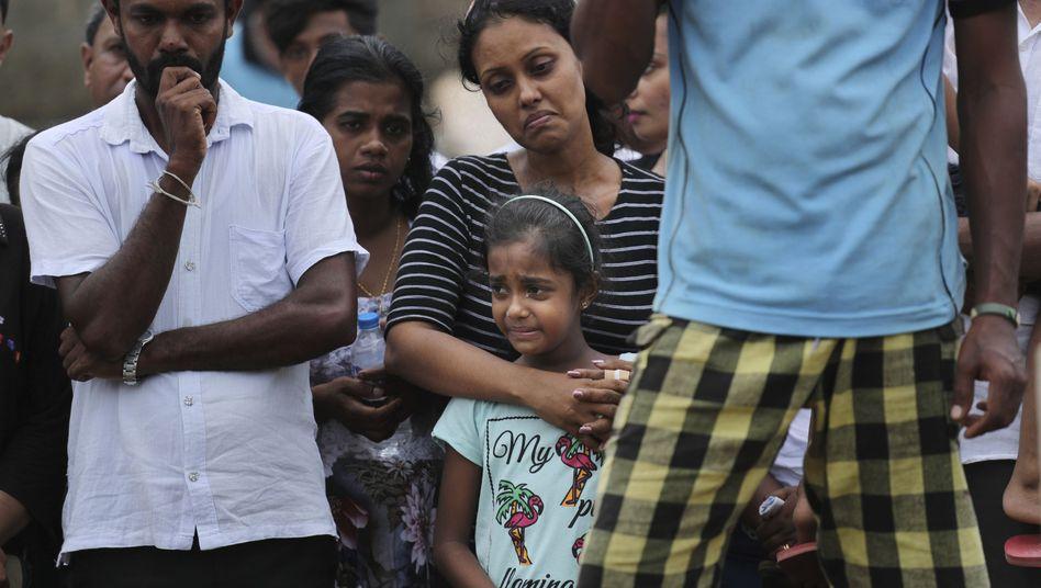 Mutter und Schwester eines Opfers der Bombenexplosionen in Sri Lanka trauern während der Beerdigung