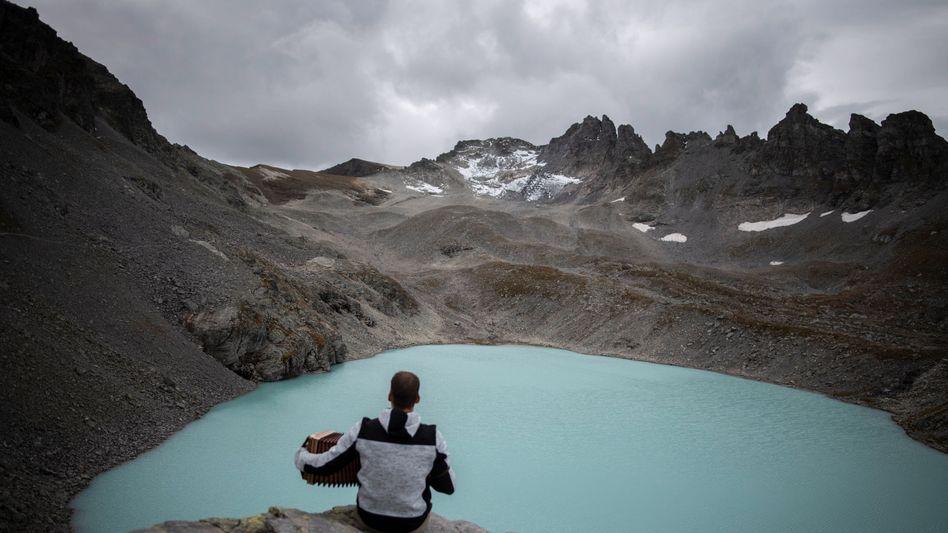 Ein Mann spielt Akkordeon an einem See unterhalb des Pizol-Gletschers