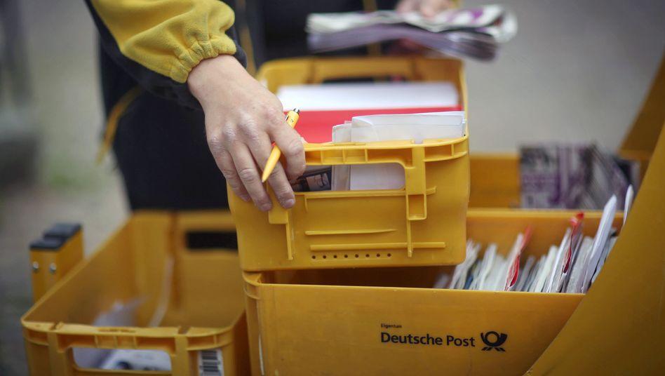 Mitarbeiter der Deutschen Post an seinem Briefzustellerwagen