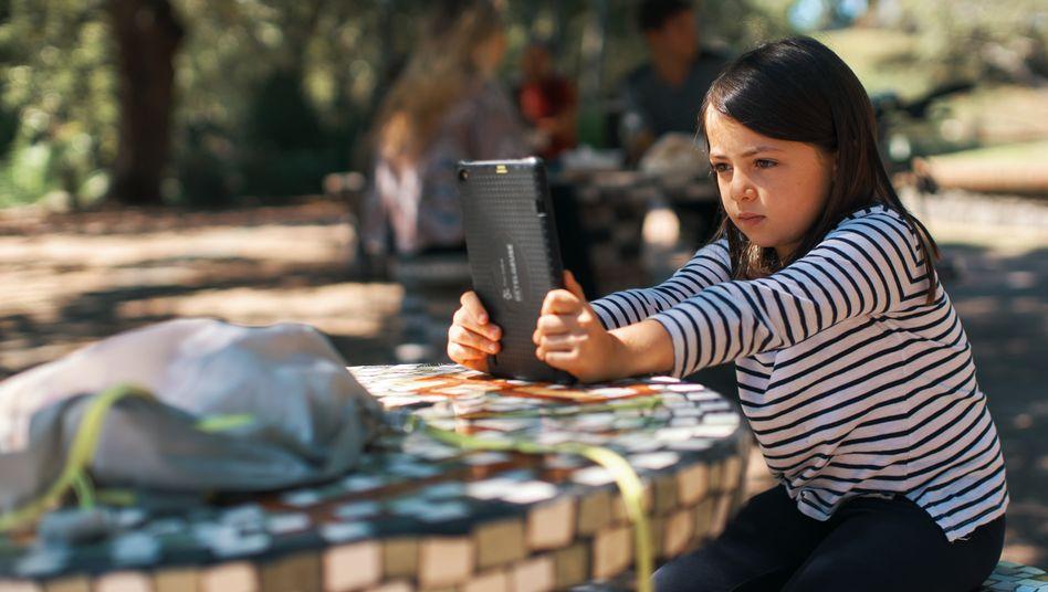 Die Grundschülerin Amelia, 7, lernt mit ihrem vom Staat gestellten Tabletcomputer in einem Park in Montevideo