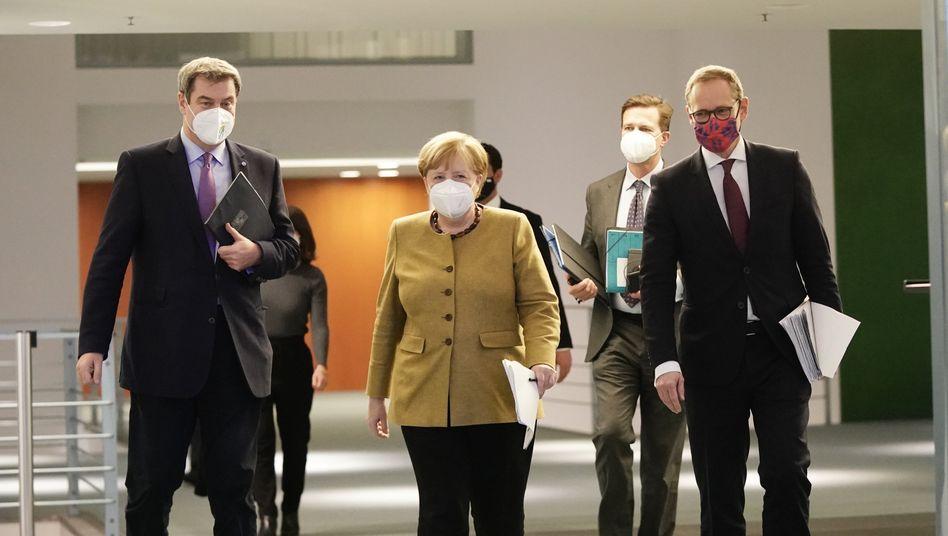 Söder, Merkel und Müller auf dem Weg zur Pressekonferenz am Dienstag: Enorme Topflappigkeit
