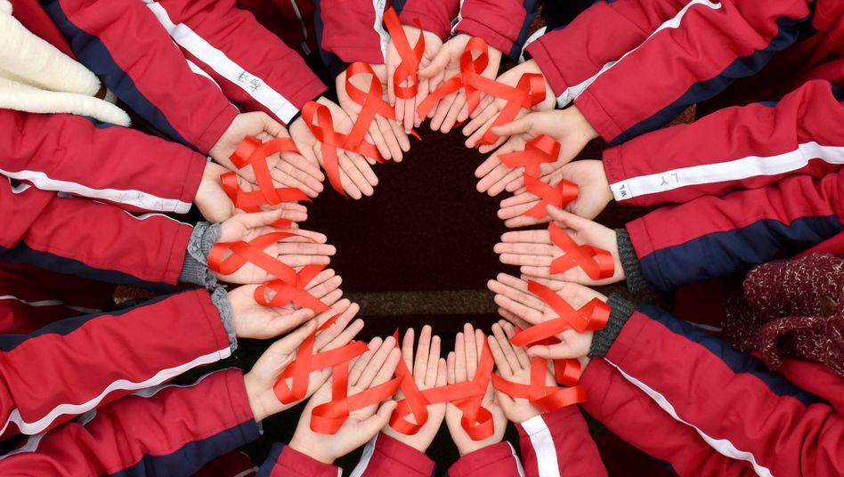 Studenten halten in China Aids-Schleifen in der Hand