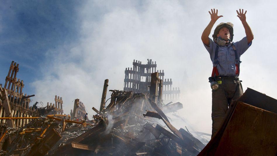 11. September 2001: Ein New Yorker Feuerwehrmann ruft in den Trümmern des World Trade Centers um Hilfe