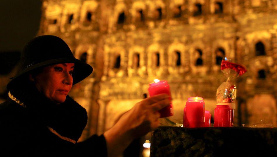 Eine Frau zündet eine Kerze vor dem Trierer Wahrzeichen, der Porta Nigra, an