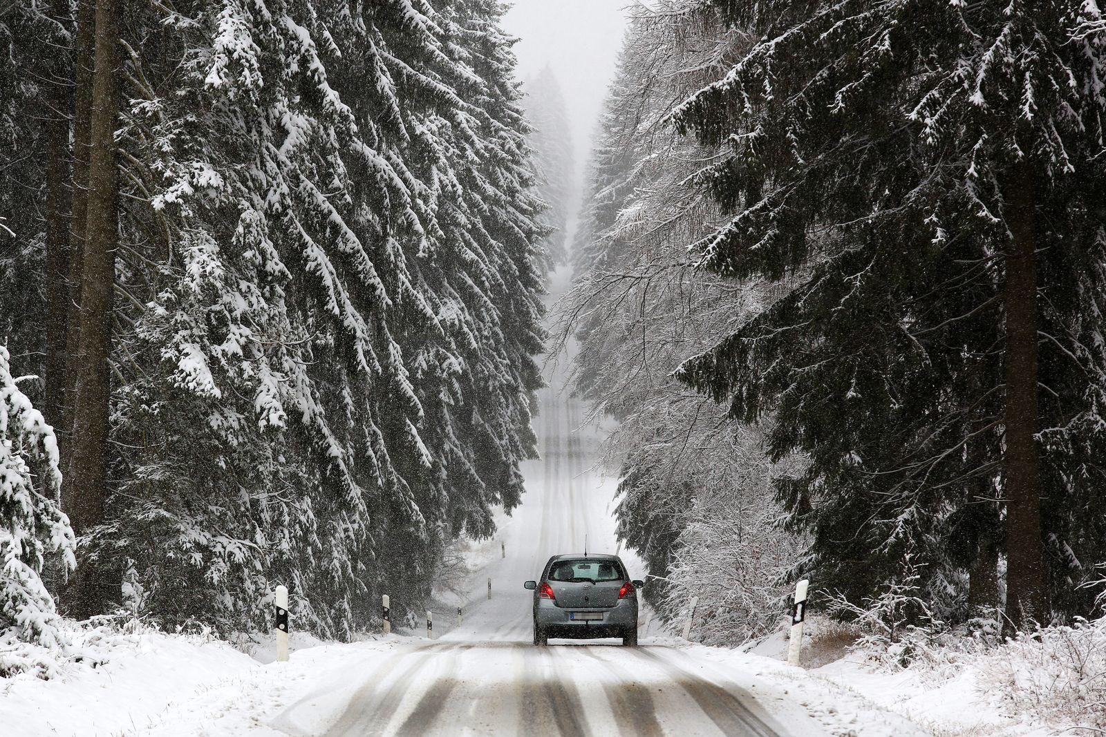 Ein Auto faehrt ueber die eingeschneite Eisenstrasse in der Naehe von Netphen-Brauersdorf Wintereinbruch im Siegerland a