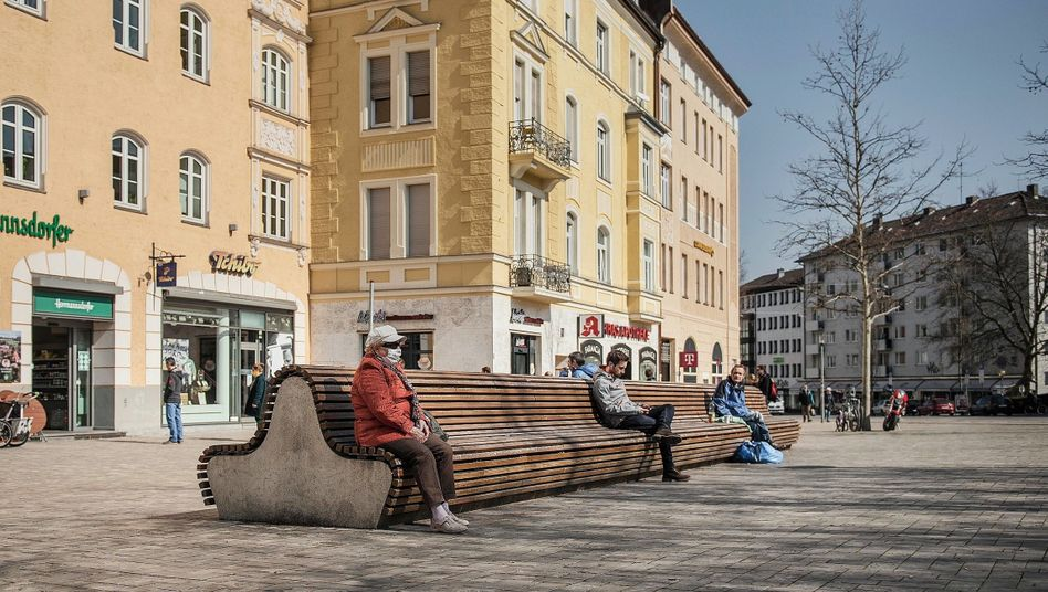 Pedestrians rest at a square in Munich, Germany