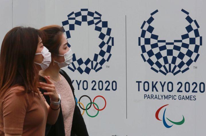Passanten laufen an einem Olympia-Plakat vorbei