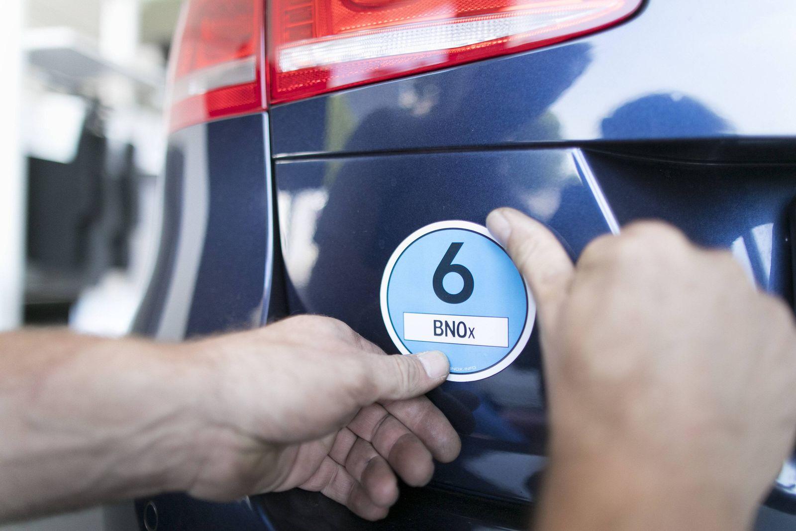 Aufkleben einer EURO NORM Plakette 6 auf ein Auto aufgeklebt Kfz Betrieb der Nachruestung von Diese