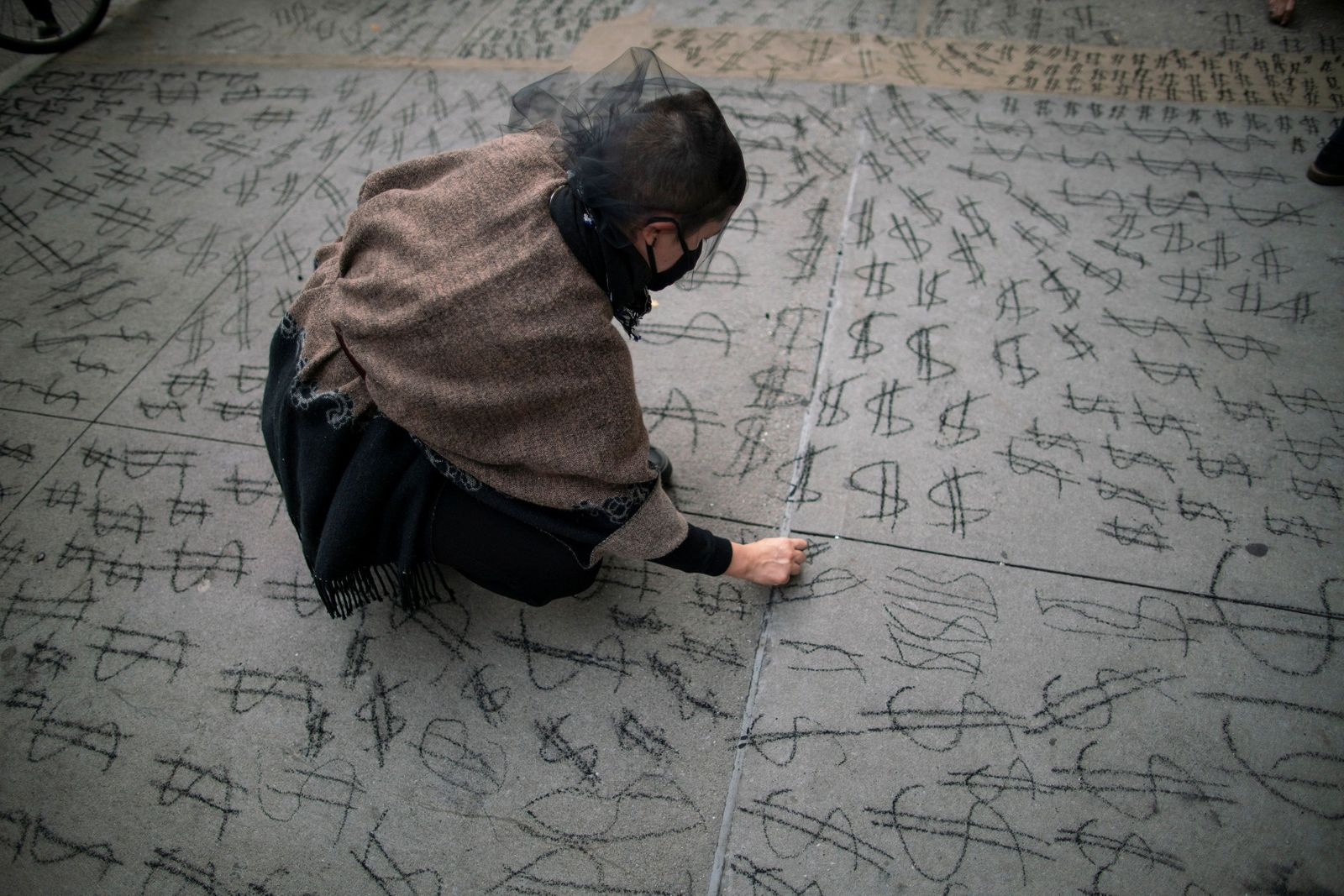 A woman paints the sidewalk with money symbols as people take part in a protest called Make Amazon Pay at the building where CEO Jeff Bezos lives in Manhattan, New York