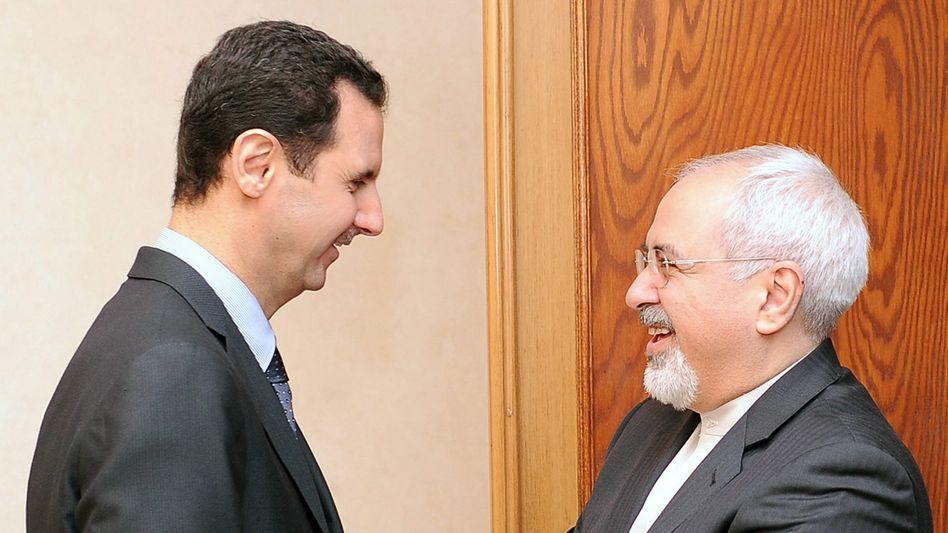 Syriens Präsident Assad (l.), Irans Außenminister Sarif: Nur Teheran kann Druck ausüben