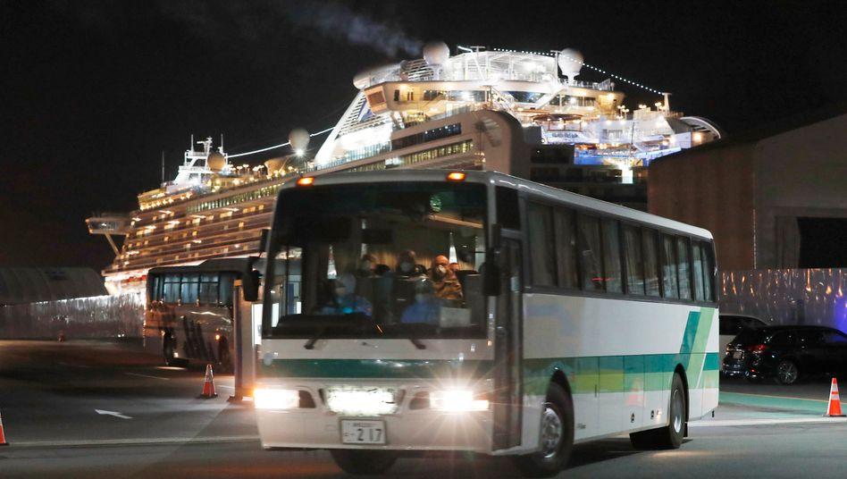 """Ein Bus mit europäischen Passagieren des Kreuzfahrtschiffs """"Diamond Princess"""" verlässt den Hafen von Yokohama (Japan)"""