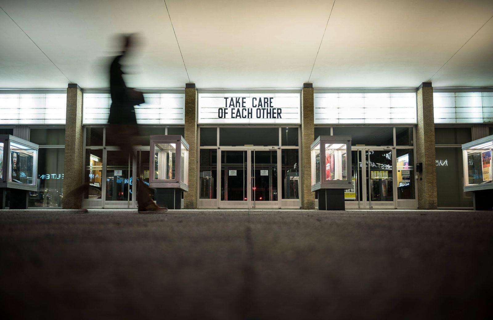 Der Schriftzug Take care of each other steht an der Fassade des Kino International in Berlin Mitte. Foto: bildgehege Ges