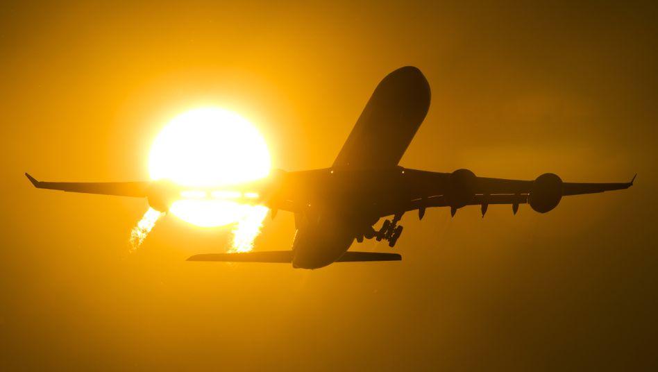 Flugzeug startet vom Frankfurter Flughafen in den Sonnenuntergang (Archiv)