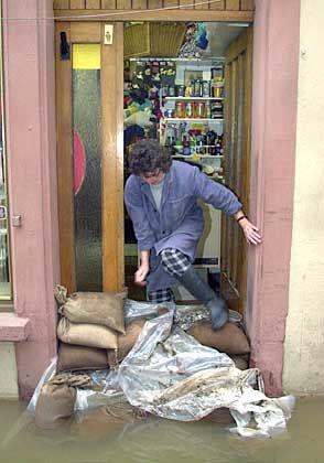 Mit Sandsäcken gegen die Fluten: Eine Frau in ihrem Geschäft in der Altstadt von Wertheim