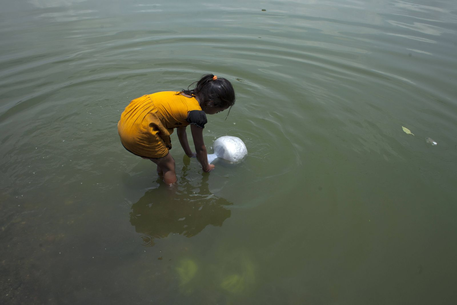 A slum child collect water from a pond for their family needs near Dhaka Daily Life Bangladesh PUB
